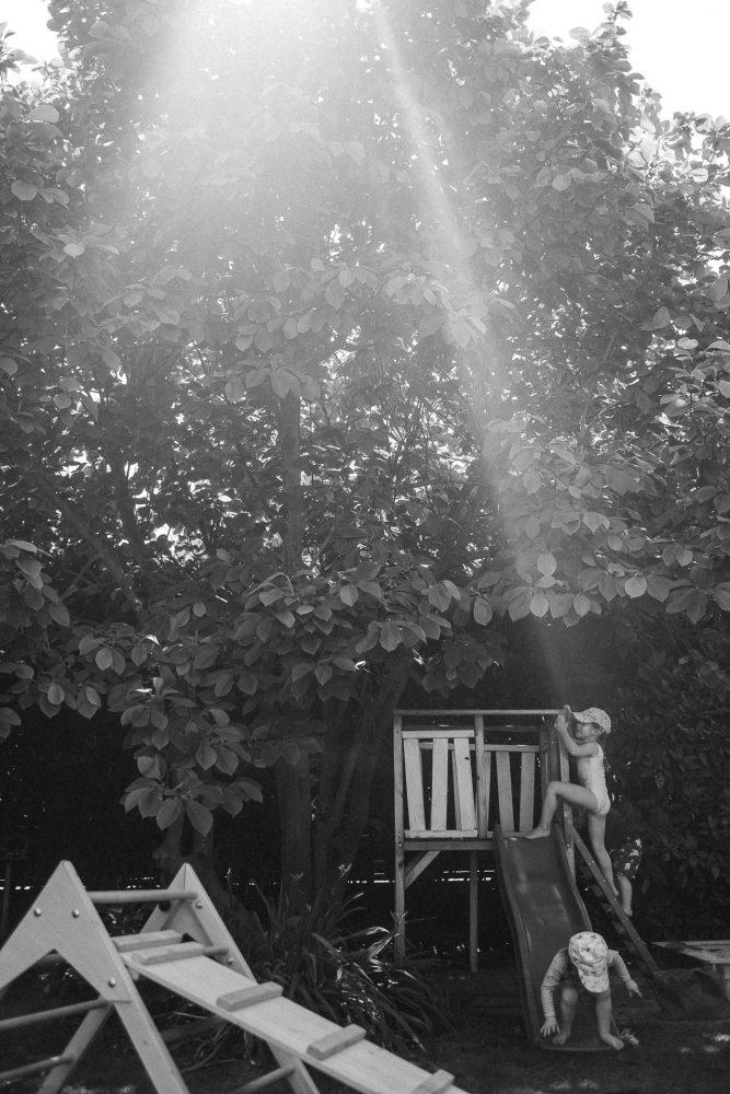 kleines Mädchen klettert im Sommer im Garten