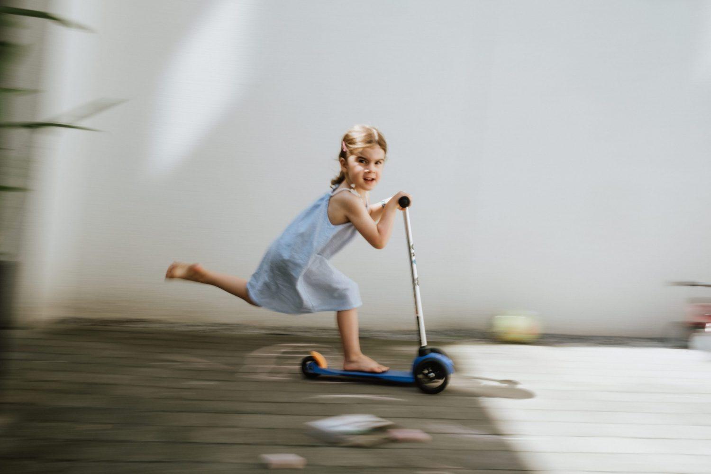 Mädchen fährt auf Roller vor weißer Wand