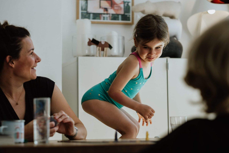 Mädchen und Mama spielen am Tisch ein Spiel