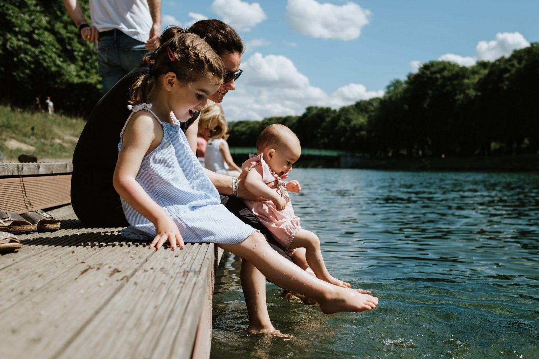 Familie sitzt am See und hält die Füsse ins Wasser