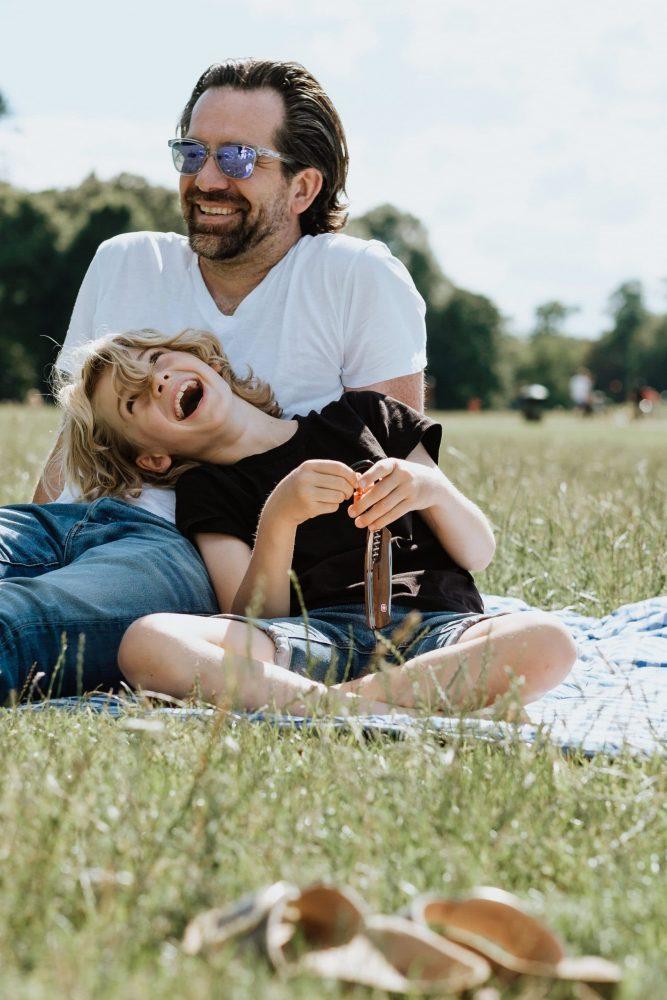 Vater und Sohn sitzen im Park auf einer Picknickdecke