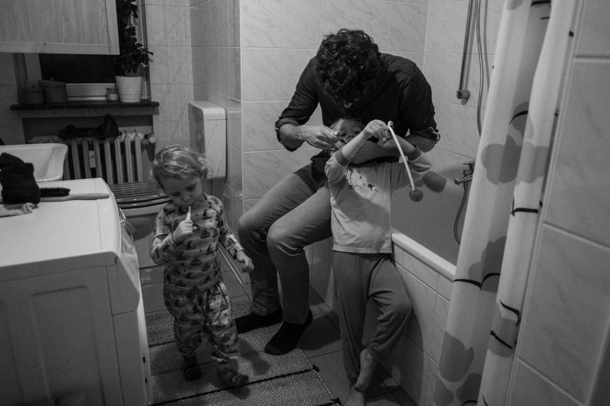 Papa putzt einem seiner Kinder die Zähne im Badezimmer