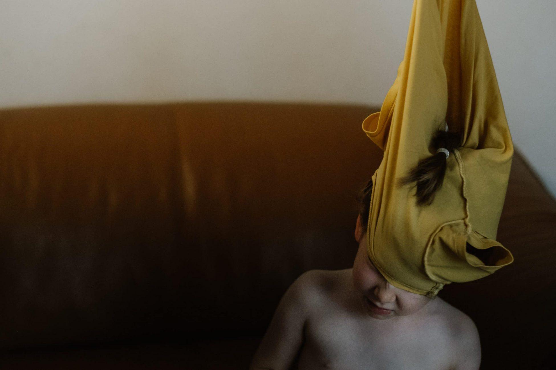 Einem Kind wird das T Shirt über den Kopf gezogen